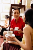 Women sitting, talking, holding cups and saucers - Alex Microstock02