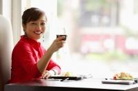 Woman sitting at table, raising drink towards camera, smiling - Alex Microstock02