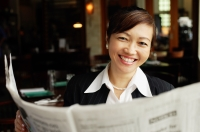 Businesswoman holding newspaper, smiling - Alex Mares-Manton
