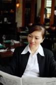 Businesswoman in restaurant, reading newspaper - Alex Mares-Manton