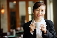 Businesswoman in restaurant, holding cup, looking at camera - Alex Mares-Manton