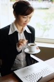 Businesswoman looking at laptop, holding cup and saucer - Alex Mares-Manton