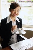 Businesswoman holding cup and saucer, smiling at camera - Alex Mares-Manton