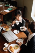 Two businesswomen at cafe, drinking coffee, laptop on table - Alex Mares-Manton