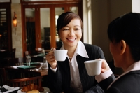 Two businesswomen at cafe, holding cups, smiling - Alex Mares-Manton