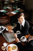 Two businesswomen at cafe with laptop - Alex Mares-Manton