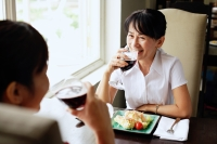 Two women at restaurant, sitting face to face, drinking wine, food on the table - Alex Microstock02