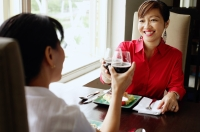 Two women at restaurant, toasting with wine glasses - Alex Microstock02