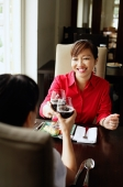 Two women toasting with wine glasses, sitting in restaurant - Alex Microstock02