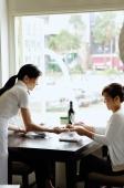 Two women in restaurant, waitress serving food - Alex Microstock02