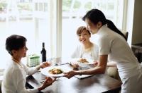 Two women in restaurant, waitress serving their food - Alex Microstock02