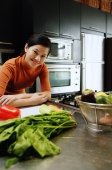 Woman in kitchen, leaning on kitchen counter, looking at camera - Alex Microstock02