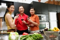 Three women in kitchen, holding wine glasses, looking at camera - Alex Microstock02
