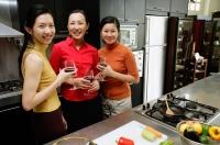 Three women in kitchen, holding wine glasses, smiling at camera - Alex Microstock02