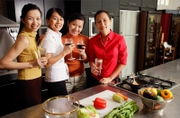 Four women in kitchen, holding wine glasses, smiling at camera - Alex Microstock02