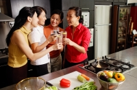 Women in kitchen, holding wine glasses, toasting - Alex Microstock02