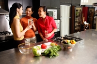 Three women in kitchen, holding wine glasses, talking - Alex Microstock02
