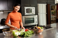 Woman cutting vegetables in kitchen, smiling at camera, portrait - Alex Microstock02