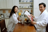 Couple having breakfast, smiling at camera, man holding newspaper - Alex Microstock02