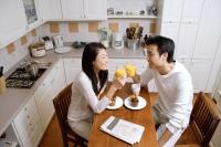 Couple in kitchen, having breakfast, holding glasses of orange juice - Alex Microstock02