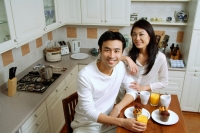 Couple in kitchen, smiling at camera - Alex Microstock02