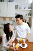 Couple having breakfast in kitchen, smiling at each other - Alex Microstock02