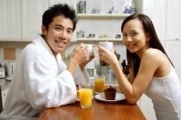 Couple in kitchen, having breakfast, smiling at camera - Alex Microstock02