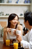 Couple in kitchen, having breakfast, both holding mugs - Alex Microstock02
