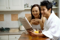 Couple in kitchen, having breakfast, looking at newspaper - Alex Microstock02