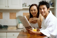 Couple in kitchen, man holding newspaper, smiling at camera - Alex Microstock02