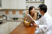 Couple in kitchen, having breakfast, man holding newspaper - Alex Microstock02