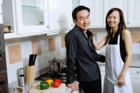 Man and woman standing in kitchen, smiling at camera - Alex Microstock02