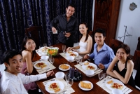 Adults at a dinner party, sitting around table, smiling at camera - Alex Microstock02