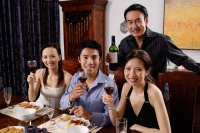 Adults at dining table, smiling at camera, raising wine glasses - Alex Microstock02