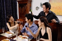 Adults at dining table toasting with wine glasses - Alex Microstock02