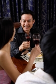 Adults holding wine glasses, sitting at table - Alex Microstock02