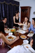 Couples having dinner at home, woman serving food - Alex Microstock02