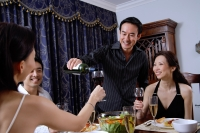 Couples having dinner party at home, man pouring wine for woman - Alex Microstock02