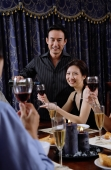 Couples at home around dinner table, man pouring wine for woman, smiling at camera - Alex Microstock02