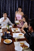 Couples having dinner party at home, woman serving food - Alex Microstock02