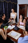 Friends around dining table, woman serving cake to man at head of table - Alex Microstock02
