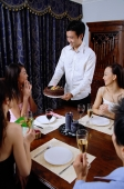Friends around dining table, man passing cake to woman at head of table - Alex Microstock02