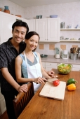 Couple standing in kitchen, woman chopping vegetables, smiling at camera - Alex Microstock02