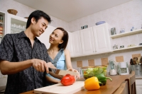 Couple in kitchen, man cutting vegetables, woman smiling at him - Alex Microstock02
