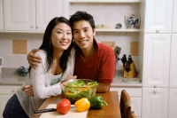 Couple leaning on kitchen counter, smiling at camera - Alex Microstock02