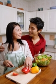 Couple in kitchen, smiling at each other, woman cutting vegetables - Alex Microstock02