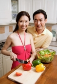 Couple in kitchen, woman chopping vegetables, smiling at camera - Alex Microstock02