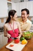 Couple in kitchen, woman chopping vegetables, looking over shoulder, smiling at man - Alex Microstock02