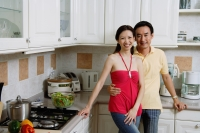 Couple standing in kitchen, smiling at camera, portrait - Alex Microstock02