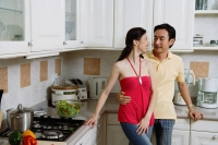 Couple standing in kitchen, smiling at each other, portrait - Alex Microstock02
